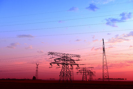 The setting sun under intensive high voltage towers  photo