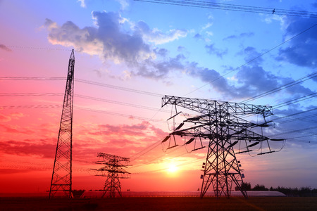 The setting sun shapes under high voltage towers  photo