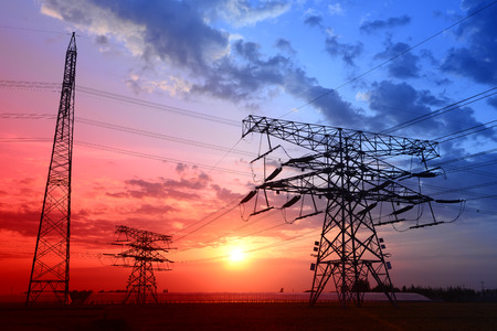 The shapes under high voltage towers in the field of the sunset    photo