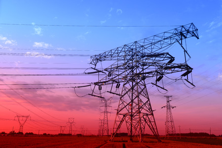 The setting sun under intensive high voltage towers in the fields photo