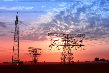 A variety of shapes of standing in the field of high voltage towers under the setting sun photo