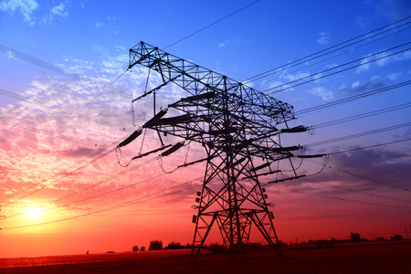 The setting sun under an isolated high voltage towers in the fields photo