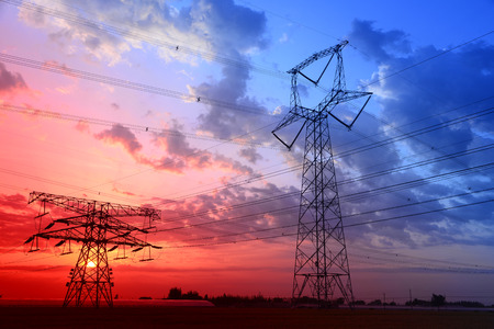 Under the sunset stands high voltage towers photo