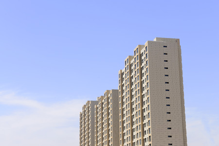towering: Towering high-rise residential building under the blue sky