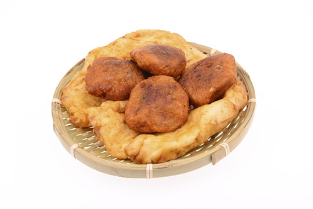 Bamboo basket inside the Fried cakes and Fried bread on a white background