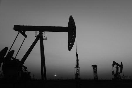 Is operation of pumping unit, silhouette in the setting sun  Stock Photo