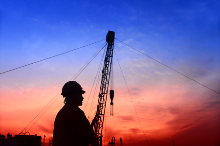 Pumping unit in the work, under the background of the setting sun  Stock Photo