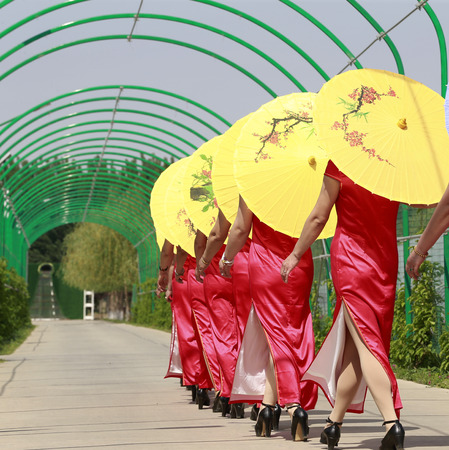 Women in cheongsam are walking