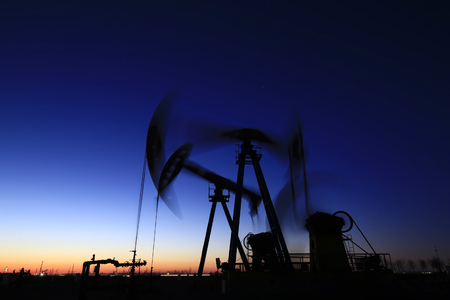 The pumping unit is at work in the evening of the oilfield Stockfoto