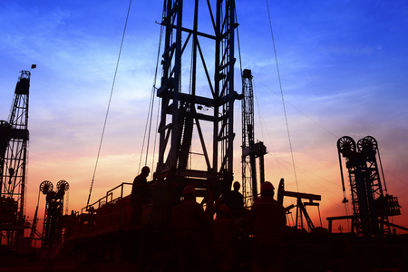 The pumping unit is at work in the evening of the oilfield Stock Photo