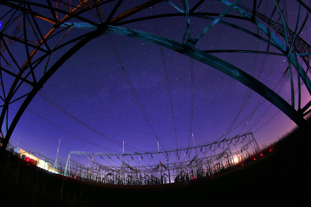 At night, the high voltage tower and substation, in a beautiful starry sky background