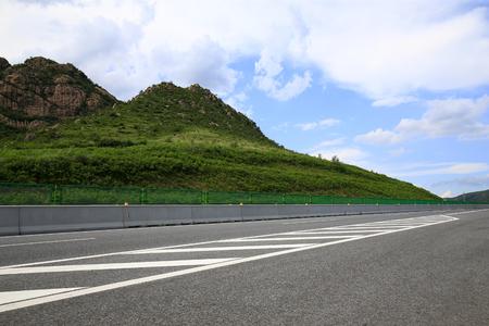 Carretera, bajo el fondo de cielo azul y nubes blancas Foto de archivo