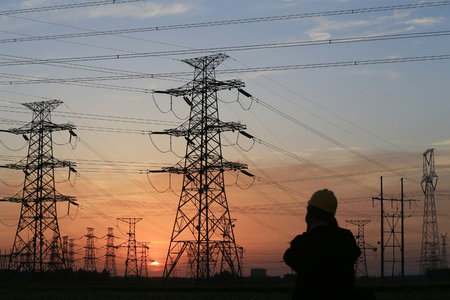 A silhouette of a high voltage tower at sunset