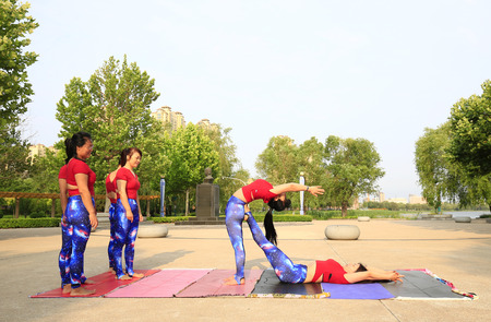 Luanan county - June 21, 2019: many women practice yoga in a park 에디토리얼