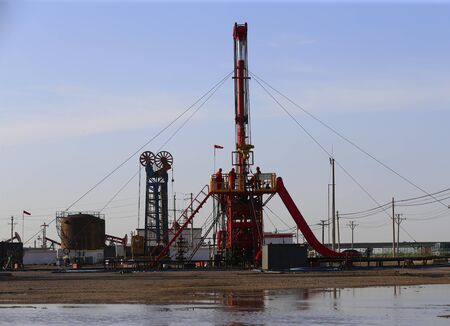 The pumping unit is operating in the oil field in the evening, silhouetted against the sky