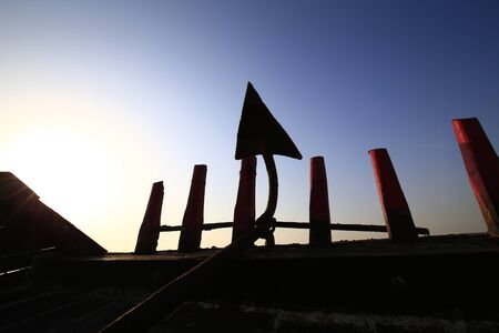 An iron anchor anchored the ship,silhouetted in the sunset Stockfoto