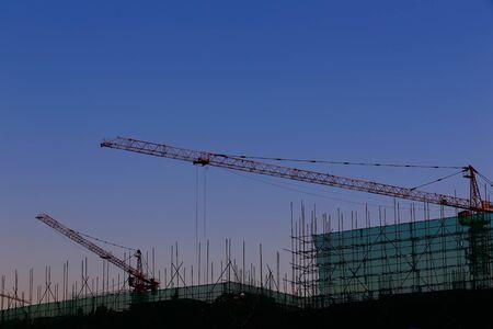 La grúa está trabajando en el sitio de construcción. Foto de archivo