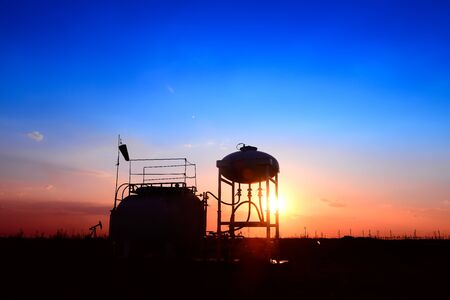 Oil tanks, silhouetted against the setting sun