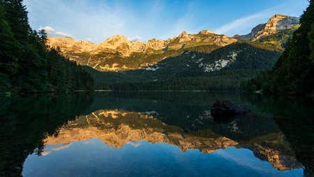Mountains reflected at dawn into Tovel lake water, Italy Imagens