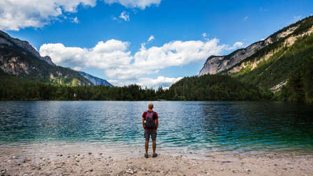 Hiker wearing a backpack and enjoying the view from Tovel Lake beach in South Tyrol, Italy
