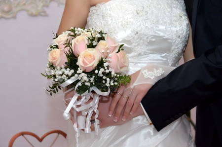 Hands of groom and fiancee with flowers