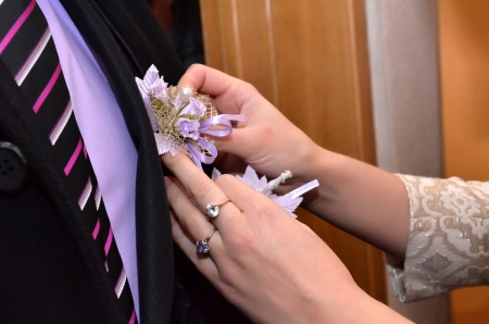 Fiancee puts a wedding flower on to the groom