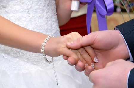 A groom puts a ring on to fiancee