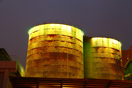 corrosion: Cement silo and production building at night