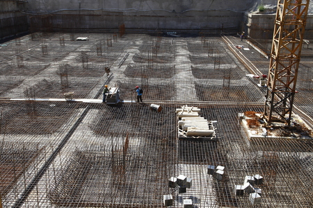 construction site: worker in the construction site making reinforcement metal framework for concrete pouring Editorial