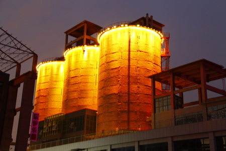 damage control: Cement silo and production building at night