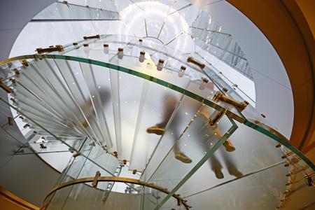 モダンなガラス階段シルエットで歩いている人は中国を上海します。