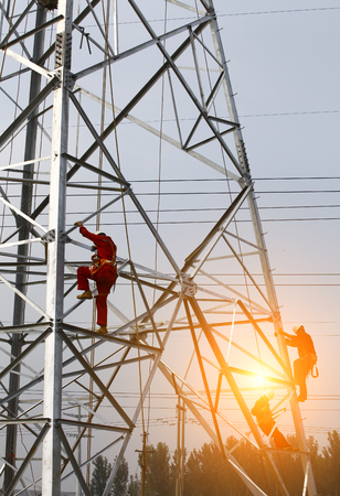 The workers working on a pylon