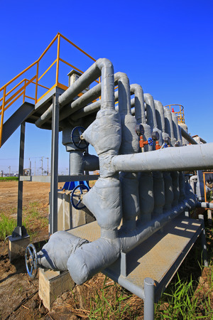 Oil pipes and valves in an oil field Stock Photo