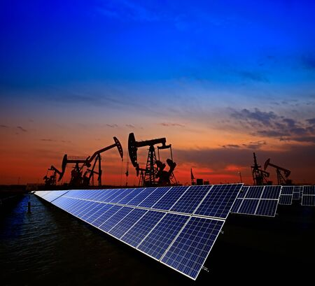 Clean power energy concept,Oil pump with solar panels and the sunset