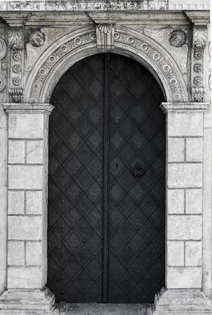 old church textured door with stone arch facade Standard-Bild