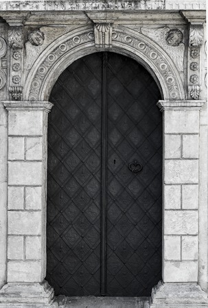 vintage door: old church textured door with stone arch facade Stock Photo