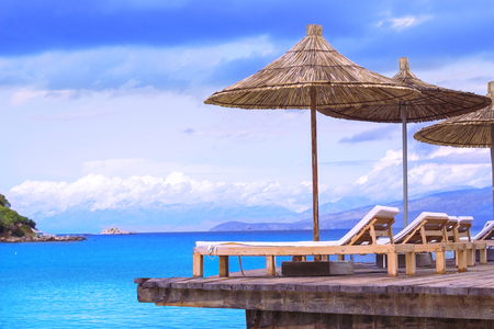 horison: Beach chairs with umbrella on wood terrace and beautiful tropical sea views Stock Photo