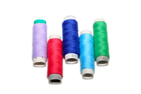 close up of color thread spool in white background photo