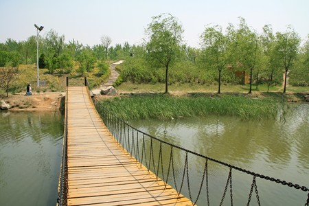 wood bridge in a park in spring, TangShang, HeBei, North China. Stock Photo - 7456966