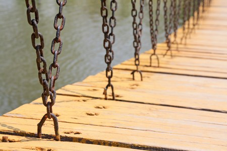 coherent: wood and iron chains of bridge in a park.