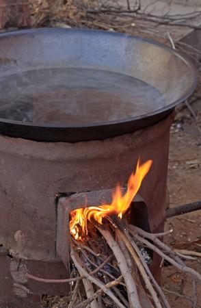 burning wood stove with iron pot, closeup. photo
