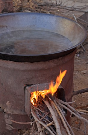burning wood stove with iron pot, closeup. photo