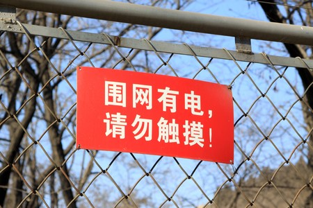 warning signs on the barbed wire fence in a zoo, Tangshan, Hebei Province, china. Stock Photo - 7475041