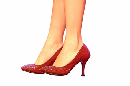 crus: pair of female legs wearing high heeled shoes, isolated on white background.