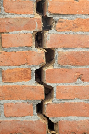 cracks in red brick wall photo