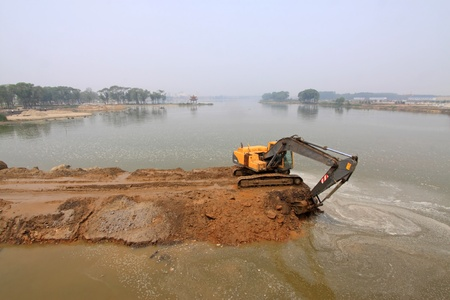 mechanization: excavator in a dam construction site in china Stock Photo