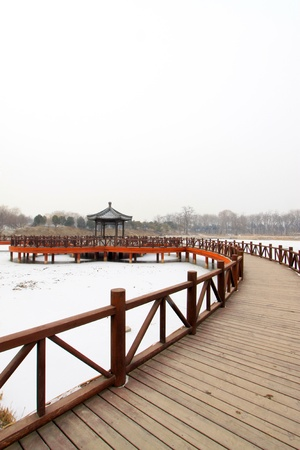 Chinese traditional style wooden bridge in the snow in a park photo