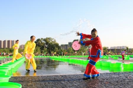 spruzzi acqua: Luannan 21 agosto: 7 luglio giorno vigilia, Diverse ragazze che spruzzano acqua a giocare in piazza, Luannan, Hebei, Cina