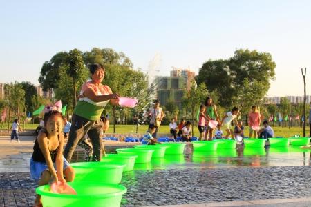 spruzzi acqua: Luannan 21 agosto: 7 luglio giorno vigilia, Diversi bambini che spruzzano acqua a giocare in piazza, Luannan, Hebei, Cina Editoriali