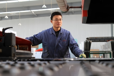 Luannan, November 24, 2012  A worker was operating CNC machine tools, in the DingRe Solar Energy Ltd, in November 24, 2012, Luannan County, china  The DingRe Solar Energy Ltd is the largest solar energy equipment manufacturers in Hebei province